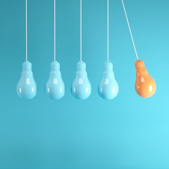 Hanging light bulbs with glowing one different idea on light blue background