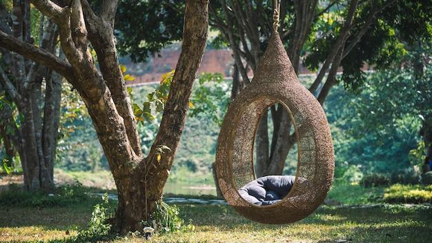 ぶら下がっている屋外の木製の卵の椅子
