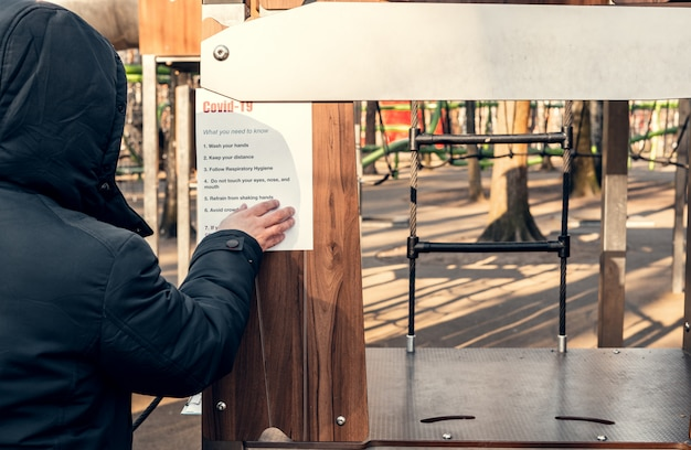 Hanging a paper on an empty playground in a park