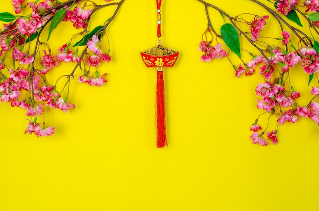 Подвесной кулон для китайского новогоднего украшения (значение слова - богатство) с китайскими цветочными цветами на желтом фоне.