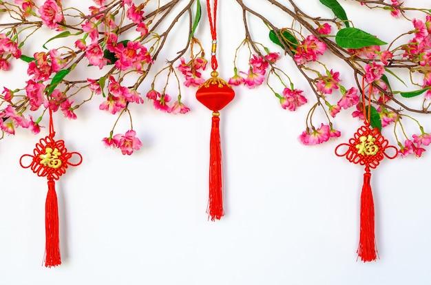 Подвесные подвески для китайского новогоднего украшения (значение слова - богатство) с китайскими цветочными цветами на белом фоне.