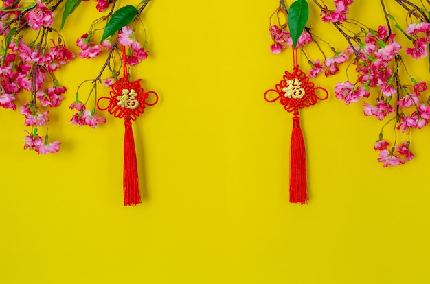Подвесные подвески для китайского новогоднего украшения (значение слова - богатство) с китайскими цветочными цветами на желтом фоне.