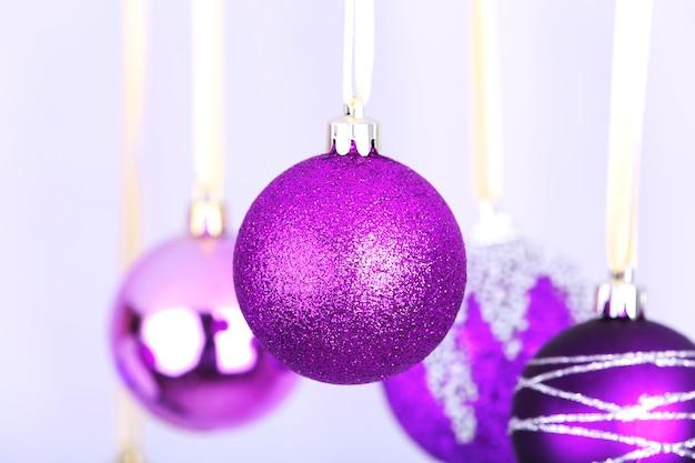 Висячие фиолетовые елочные игрушки на светлом фоне