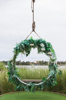 Висячие старинные деревянные качели украшены цветами и листьями. дизайн для декора места на открытом воздухе.