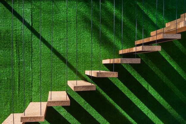 Hanging wooden stairs on artificial grass wall