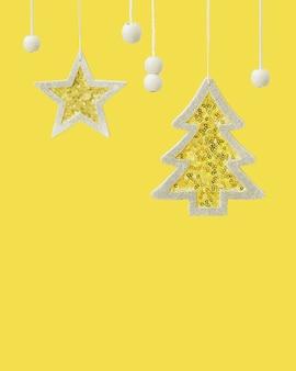 ぶら下がっている黄色い星と銀の輝くスパンコールの冬のお祝いとクリスマスツリーのおもちゃ