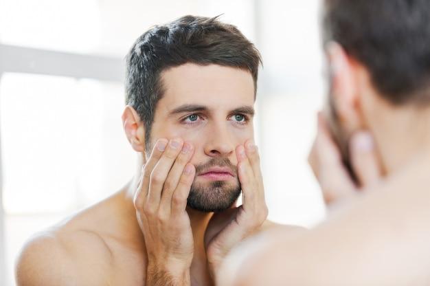 夜の外出後の二日酔い。鏡に向かって立っている間、彼の顔に触れて、彼自身を見ている欲求不満の若い上半身裸の男