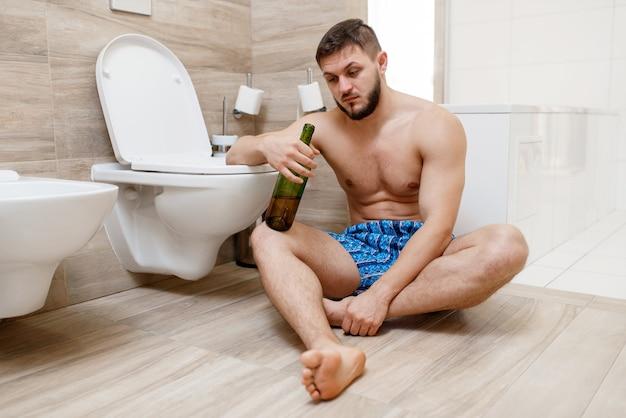 バスルームのトイレの近くの床に座っているワインのボトルを持つ二日酔いの男。