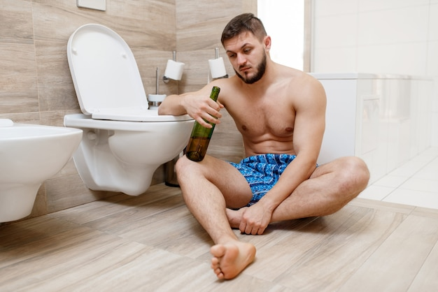 Hangover man with bottle of wine sitting on the floor near the toilet in bathroom.