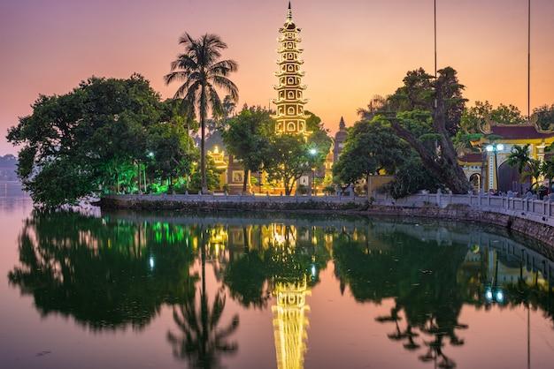 Hanoi buddhist pagoda on west lake, colorful sunset, illuminated temple, water reflection. chua tran quoc on ho tay at hanoi, vietnam travel.