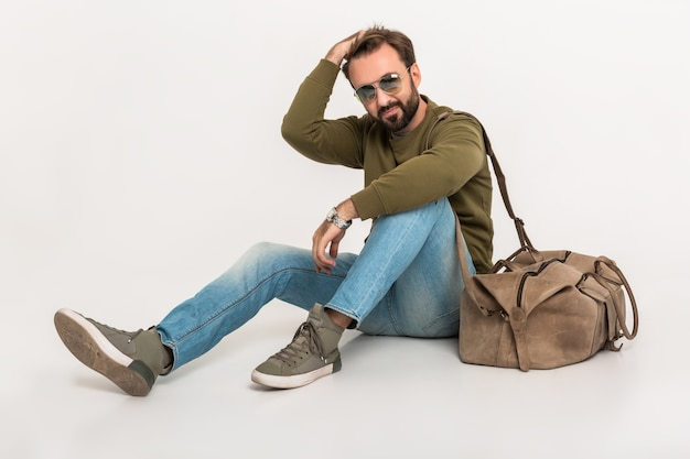Хансомный бородатый стильный мужчина сидит на полу изолированно, одетый в толстовку с дорожной сумкой, в джинсах и солнцезащитных очках