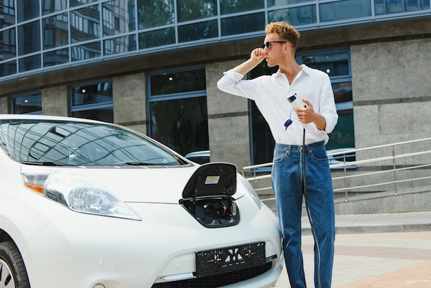 Красивый парень сидит возле своего нового современного электромобиля и держит вилку зарядного устройства, пока машина заряжается на зарядной станции