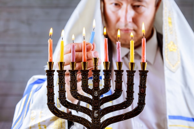 Ханука, еврейский праздник. горящие свечи в меноре, человек на заднем плане.