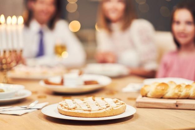 ハヌカの夕食。伝統的な料理でテーブルを囲む家族