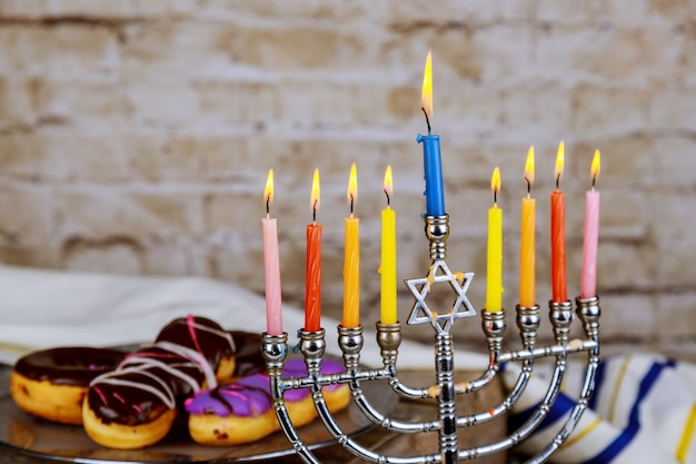 Hanukkah flatlay: hanukkah candies sufganiyot, menorah, multicolor candles