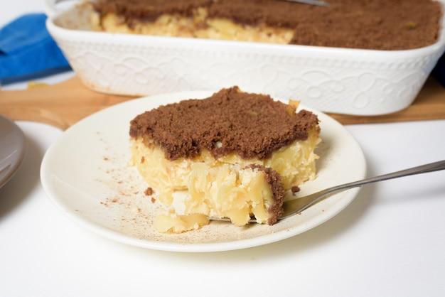 Праздник ханука, традиционный сладкий пирог кугель с лапшой и заварным кремом, сверху песочное какао-крошка. на светлом фоне в форме для запекания. кусочки пирога на тарелке.
