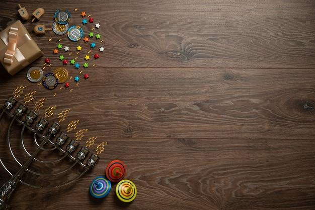 Ханука, менора, шоколадные монеты, подарки на деревянном столе. вид сверху