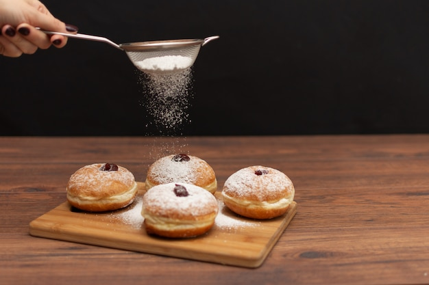 Hanukkah sufganiyot. traditional jewish donuts for hanukkah with red jam and sugar powder.