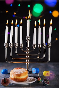 Hanukkah table setting a candlestick with candles, donut and spinning tops on blue