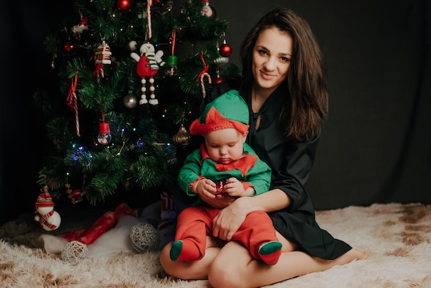 Happ mother sitting with baby little boy son at christmas tree