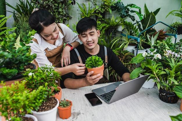 Felicemente coppia di giardinieri usa il computer portatile mentre tutorial online sui piani in vaso in officina insieme