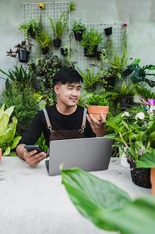 Felicemente giardiniere usa smartphone e computer portatile mentre tutorial online sui piani in vaso in negozio