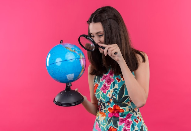 Happily smiling young traveler woman holding earth globe and magnifier glass on isolated pink wall
