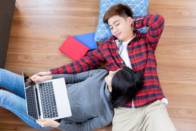 Happily young man and pretty woman lying on the wooden floor and using laptop