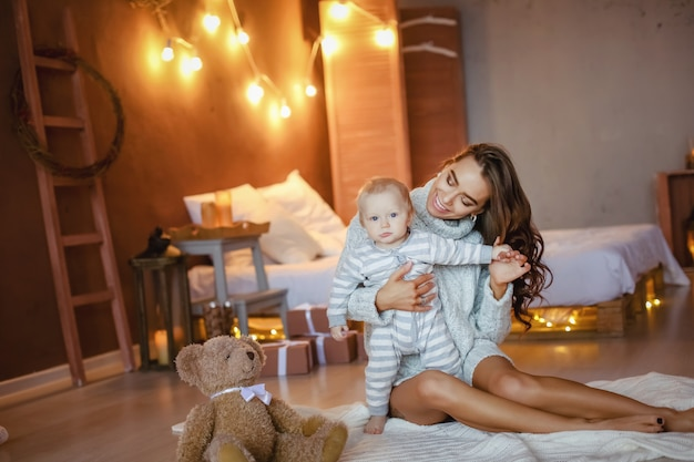 Happines baby in the arms of a beautiful mother in the bedroom