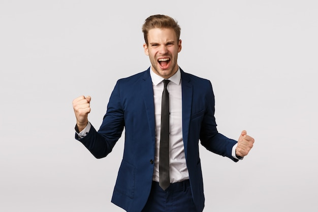 Happiness, achievement and business concept. handsome confident and triumphing young businessman made lots money, signed deal, clench fists and yelling champion, feel upbeat, white background