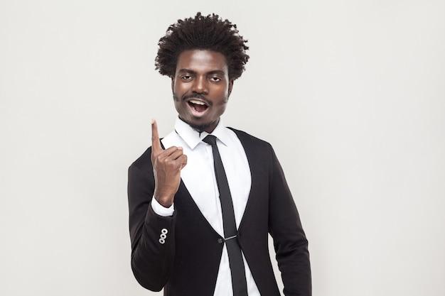 Человек счастья афро смотря камеру с пальцем идеи. студийный снимок, серый фон