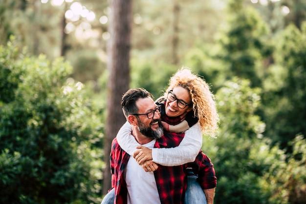 幸せと陽気な人々は、森の田舎で一緒に遊んで楽しんでいる楽しいカップルと競争します-大人の男性と女性が屋外で一緒にたくさん運んで笑っている関係にあります