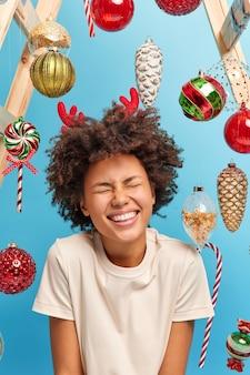 행복과 축제 이벤트 개념. 기쁜 즐거운 어두운 피부를 가진 여인이 웃고 눈을 감고 미소를 지으며 크리스마스 트리를 장식 할 것입니다. 캐주얼 화이트 티셔츠를 입고 겨울 휴가를 즐깁니다.