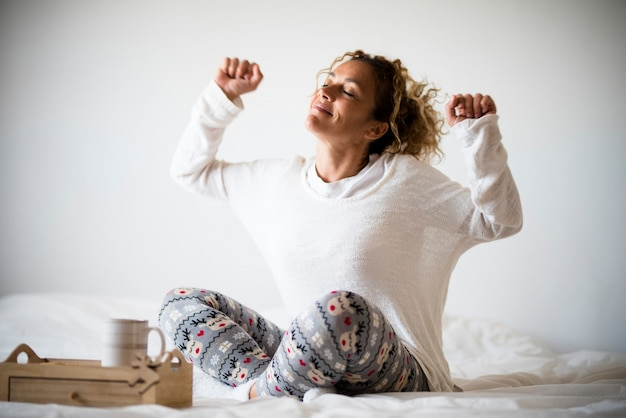 Концепция счастья и хорошей жизни со счастливой взрослой молодой женщиной, просыпающейся и наслаждающейся утренним светом - дома или в гостиничном номере - люди просыпаются и ведут приятный образ жизни