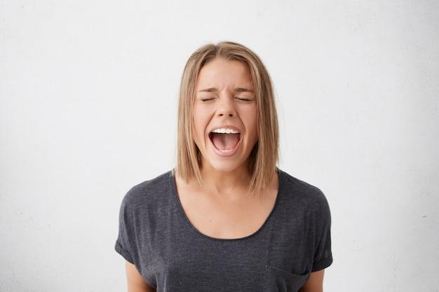 幸福と喜びの概念。目を閉じて口を開けて叫んで興奮しているうれしそうな美しい女性