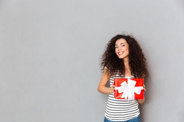 Счастье и радость выражают молодую женщину, держащую подарочную коробку с белым бантом, стоя над серой стеной