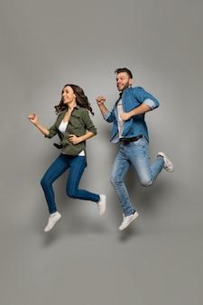 Счастья и радости. фотография в полный рост очаровательной женщины с длинными волосами, одетой в повседневную одежду, и красивого мужчины в джинсовой одежде, которые прыгают и улыбаются.