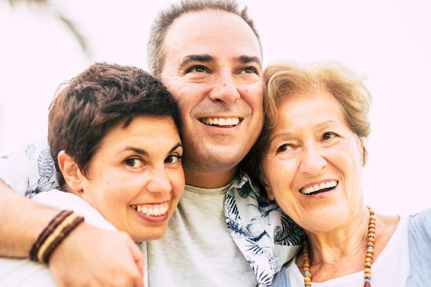 母、息子、ガールフレンドが一緒に抱き合って、澄んだ白い背景に笑顔で楽しんでいる、現代の白人の家族の幸せと喜びに満ちた接写のポートレート
