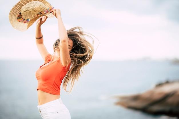 美しい白人女性との幸せと楽しい人々の概念はジャンプして楽しんでいます-夏休みのtracvel休暇と海の焦点がぼけた地平線の眺め