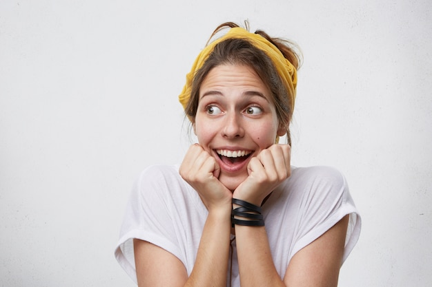幸福と成功のコンセプトです。幸せそうに振るあごの下で手をつないでよそ見する喜びに満ちた興奮した女性