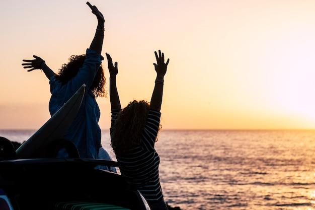 여자 젊은 친구 부부와 함께 행복과 성공적인 개념은 휴가 여름 휴가에 일몰을 즐길 수