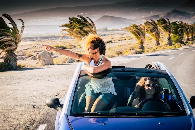 幸福と旅行のライフスタイルの人々-青いコンバーチブル車で運転して旅行している女性の大人の友人のカップル-屋根の外で旅行を見て楽しんでいるかなり巻き毛の金髪の女性 Premium写真