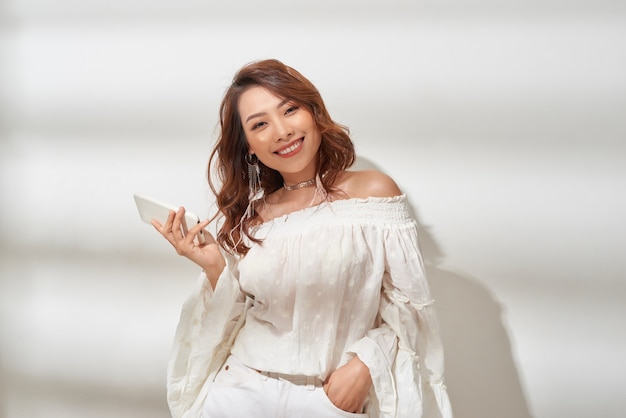 カジュアルな服を着てイヤホンでスマートフォンから音楽を聴く幸せアジアの女の子
