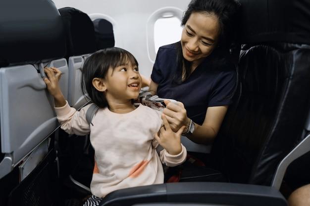 Счастье азиатской маленькой девочки в салоне самолета
