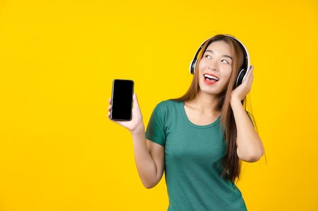 Наушники технологии счастья азиатские усмехаясь нося молодой женщины беспроволочные для слушать музыку через умный мобильный телефон на изолированной желтой стене, образе жизни и отдыхе с концепцией хобби
