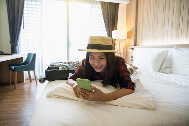 행복 아시아 여행자 여자 자고 침대에서 스마트 휴대 전화를 사용