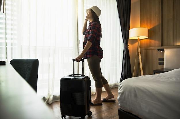 호텔이나 호스텔의 침실에 수하물을 들고 서 있는 행복 아시아 여행자 여성