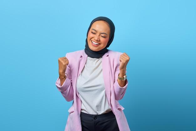 파란색 배경 위에 웃는 표정으로 성공을 축하하는 행복 아시아 여성