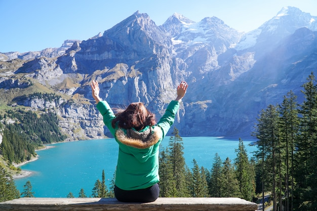 Happiness asian young traveller hiker enjoys the amazing view of oeschinensee lake