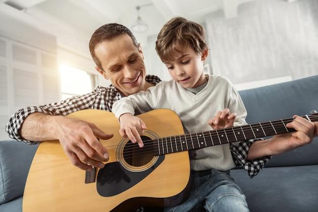 幸福。ソファに座ってギターを弾くことを学ぶ魅力的な集中した金髪の少年と彼の父親は笑っている